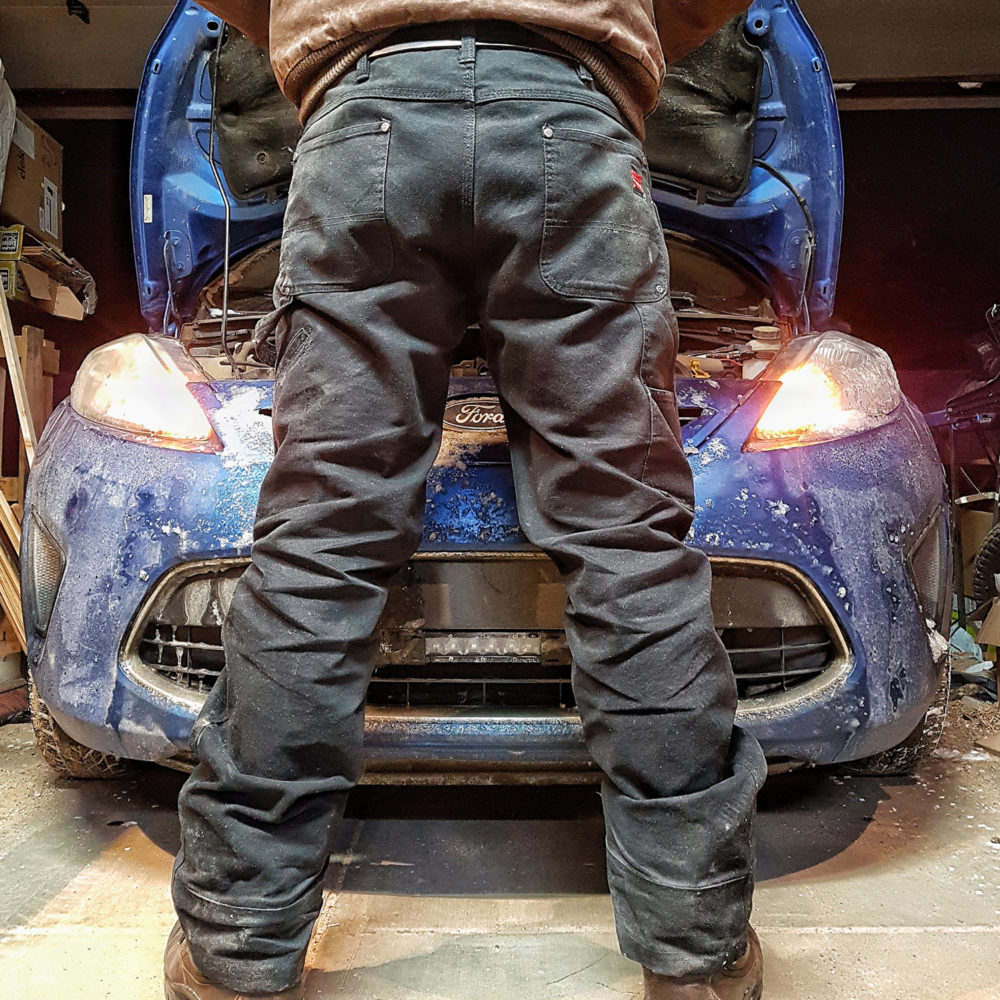 Man standing in front of car with open hood wearing black Tough Duck work pants